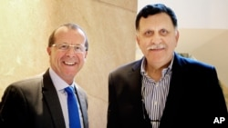FILE - In this Feb. 17, 2016 file photo, U.N. special envoy for Libya Martin Kobler, left, is greeted by Fayez Serraj, Libyan designated-prime minister and head of the presidential council, in Cairo, Egypt.
