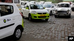 Ola cabs, left, waiting for customers, are parked next to other cars in Kolkata, India, March 29, 2016.