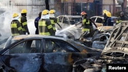 Firefighters douse cars after a bomb blast at a crowded shopping district in Abuja, Nigeria, June 25, 2014.