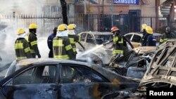 Bomberos tratan de apagar el fuego de un coche ardiendo después del bombardeo en un centro comercial en Abuja.