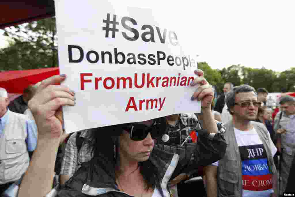 A woman holds a sign a protest against the crisis in eastern Ukraine orgainsed by the Russian communist party in Moscow ,July 3, 2014.