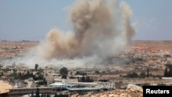 Asap mengepul setelah serangan udara oleh pasukan Suriah di Aleppo (21/5).