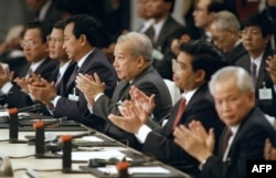 FILE - From left: Khmer Rouge factions leaders, Im Chuun Lin, Cambodian Premier Hun Sen, Dith Munty, Cambodian Prince Norodom Sihanouk, Ieng Mouly and Khieu Samphan, applaud 23 October 1991 in Paris after signning the peace treaty which ended dacades of civil war in Cambodia. (AFP/Eric Feferberg)