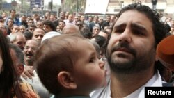 FILE - Alaa Abdel Fattah (R), one of the activists who was summoned by the public prosecutor on whether he had a role in the recent violent anti-Islamists protests, arrives with his wife and child to the public prosecutor's office in Cairo.