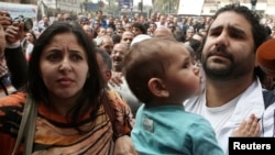 FILE - Alaa Abdel Fattah arrives with his wife and child to the public prosecutor's office in Cairo, March 26, 2013.