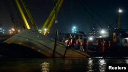 Rescue workers are seen at the site after a tug boat sank in the Yangtze River, near Jingjiang, Jiangsu province, January 16, 2015.