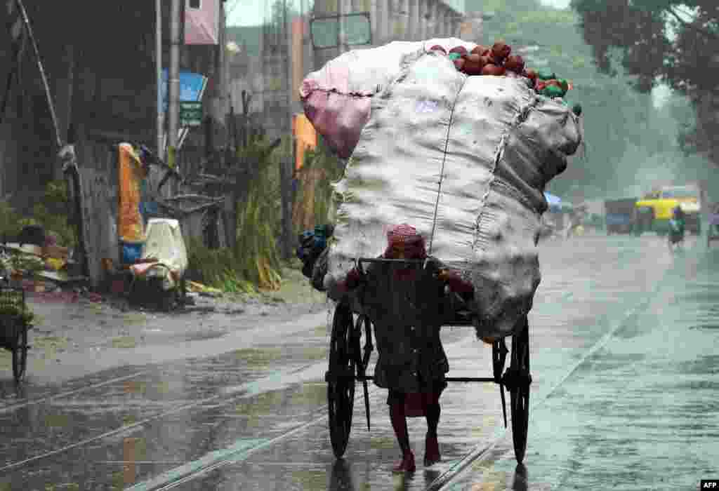 An Indian rickshaw-puller transports goods along a road in heavy rain in Kolkata.