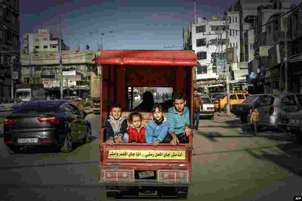 Palestinian children ride in the back of a tuktuk with their father on their way to a street market in Gaza City.