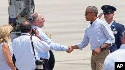Poignée de main entre le président Barack Obama et le gouverneur de Louisiane John Bel Edwards à l'arrivée de M. Obama à l'aéroport de Baton Rouge, le 23 août 2016.