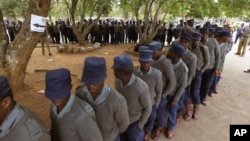 Zimbabwean police officers wait in line to cast their votes at a polling station in Harare, July 15, 2013. Early voting started for police and security personnel who will be on duty during the nation's July 31elections.