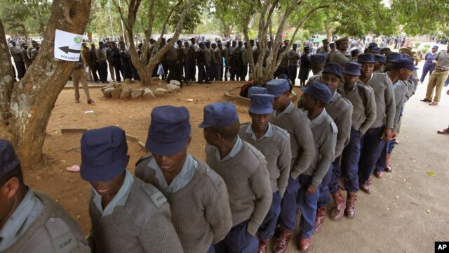 Zimbabwean police officers line up for early voting in Harare, July 15, 2013. Election officials have been accused of discarding some ballots cast by about 70,000 police and soldiers.