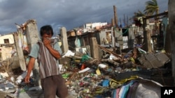 A Filipino man covers his nose from the stench a dead body found at neighborhood badly ravaged by Typhoon Haiyan in Tacloban, Philippines, Saturday, Nov. 16, 2013.