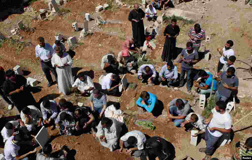 People pray during the funeral of the Free Syrian Army fighter Amar Ali Amero in Azaz, August 21, 2012.