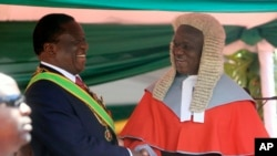 "FILE: Zimbabwean President Emmerson Mnangagwa,left, is congratulated by Chief Justice Luke Malaba after taking his oath during his inauguration ceremony at the National Sports Stadium in Harare, Sunday, Aug. 26, 2018. The Constitutional Court upheld Mnangagwa's narrow election win Friday, saying the opposition did not provide "" sufficient and credible evidence"" to back vote- rigging claims.(AP Photo/Tsvangirayi Mukwazhi)"