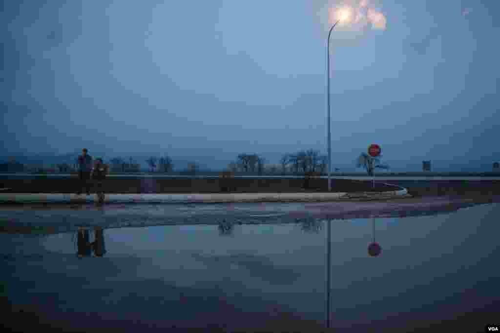 مبارزان اوکراينی پس از بازگشت از خط مقدم جبهه در نزديکی پروومائيسکه قدم می زنند و سيگاری دود می کنند. عکس از آدام بيلز از صدای آمريکا.