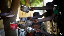 Children get their food from leftovers at a restaurant in Gao, northern Mali, Feb. 8, 2013.