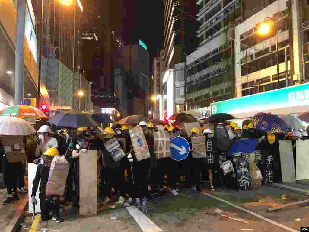 2019年7月28日晚,中環遮打花園反送中集會演變成群眾自發遊行,一批示威者在上環集結築起防線與警方防暴警察對峙。