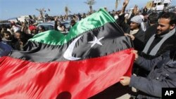 Anti-Libyan leader Moammar Gadhafi protesters wave the old Libyan flag as they celebrate the freedom of the Libyan city of Benghazi, Libya, February 28, 2011