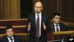 PM Arseniy Yatsenyuk (tengah) berhasil menghindari mosi tidak percaya terhadap dirinya di parlemen Ukraina hari Selasa (16/2).