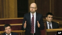 FILE - Ukrainian Prime Minister Arseniy Yatsenyuk, center, reacts after surviving a vote of no confidence, in Parliament in Kyiv, Feb. 16, 2016. Yatsenyuk said April 10, 2016, he is resigning, opening the way for a new government to be formed in an effort to end Kyiv's political crisis.