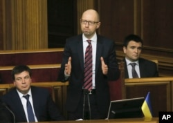 FILE - Ukrainian Prime Minister Arseniy Yatsenyuk, center, reacts after surviving a vote of no confidence, in Parliament in Kyiv, Ukraine, Tuesday, Feb. 16, 2016.