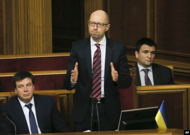 Ukrainian Prime Minister Arseniy Yatsenyuk, center, reacts after surviving a vote of no confidence, in Parliament in Kyiv, Ukraine, Tuesday, Feb. 16, 2016.