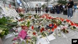 在德国杜塞尔多夫机场乘客们注视着为坠机罹难者敬献的蜡烛和鲜花。