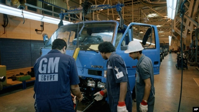 FILE - Employees work at a General Motors Egypt joint venture truck plant, just outside Cairo, Egypt.