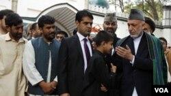 Presiden Hamid Karzai (kanan) memberikan pengampunan kepada 8 anak yang disiapkan Taliban jadi pembom bunuh diri, setelah acara shalat Ied di Kabul (30/8).