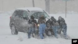 Cư dân giúp đẩy một chiếc xe bị kẹt trong tuyết tại thị trấn Bethlehem, bang Pennsylvania, ngày 13/2/2014.