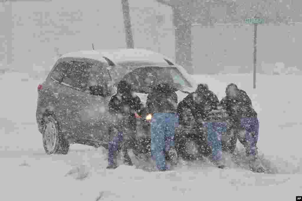 People help push a stranded motorist stuck in deep snow on Stefko Boulevard, Feb. 13, 2014 in Bethlehem, Pennsylvania.