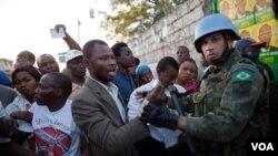 Yon gwoup elektè ayisyen ak yon sòlda mentyen lapè brezilyen, k ap diskite nan moman moun kanpe an liy ap tann tou yo pou yo ale vote nan 2zyèm tou eleksyon prezidansyèl ak lejislatif dimanch 20 mas la, nan Port-au-Prince, Haiti (AP Photo/Ramon Espinosa)