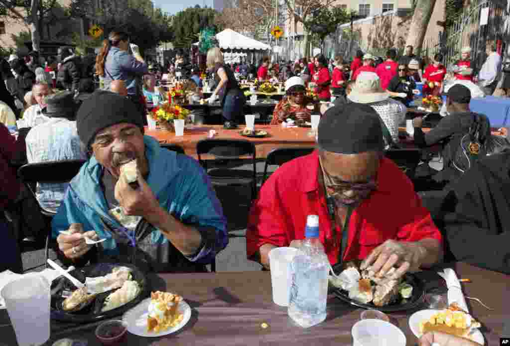 Michael Smith, left and Jerry Brown have their Thanksgiving meal with hundreds of homeless individuals, Los Angeles, California, November 21, 2012.