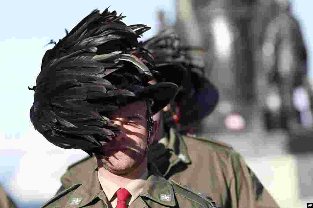 The feathered hat of an Italian Bersagliere is blown by a strong wind as he stands at attention before the meeting between Russian President Vladimir Putin and Italian Premier Enrico Letta, in Trieste, Italy.