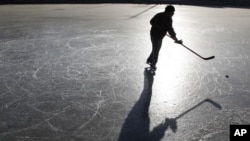 A skater plays ice hockey on a frozen lake in Beijing December 23, 2010.