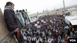 Seorang tentara Kemerdekaan Suriah berjaga saat para pengunjuk rasa melakukan demo anti-presiden Bashar Al-Asaad di Idlib, Suriah (6/2).