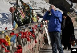 FILE - A man looks at pictures of victims of the Maidan Square protests placed in Kyiv, Ukraine, Feb. 17, 2015.