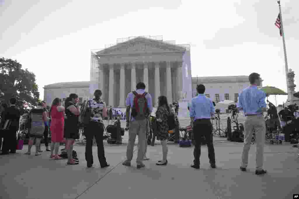 People wait outside the Supreme Court in Washington as key decisions are expected to be announced.
