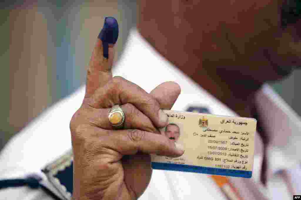 An Iraqi policeman shows his ink-stained finger after voting at a school in Baghdad.