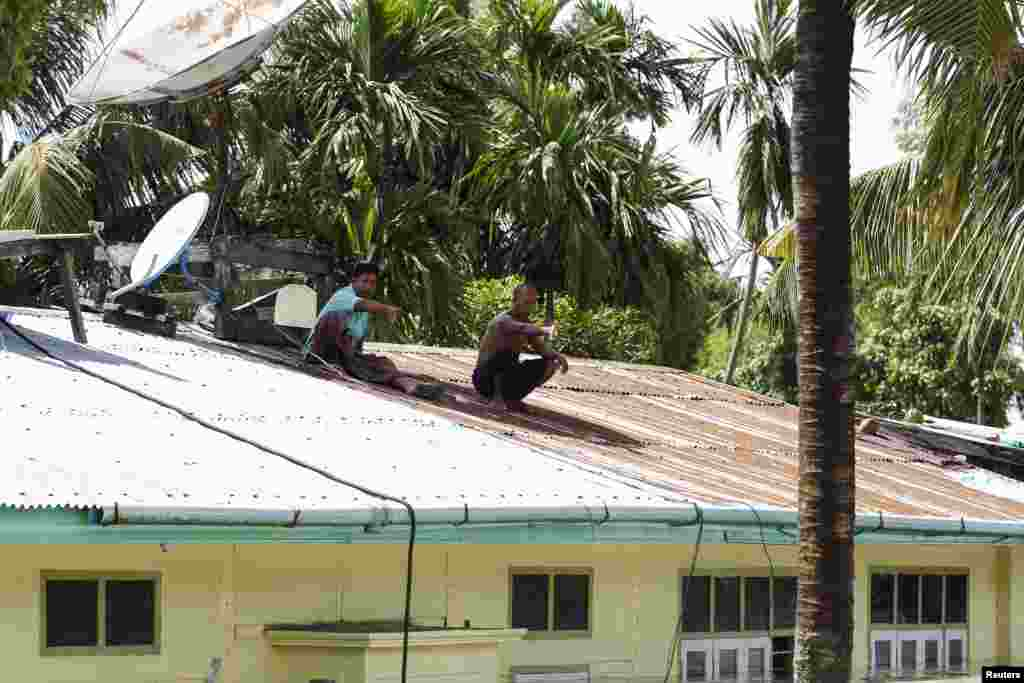 Men gesture on the roof of a home in a flooded village at Kalay township, Sagaing region, Aug. 2, 2015.