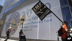 Protesters carry placards and an effigy of a shark outside the International Monetary Fund (IMF) headquarters building during the annual IMF-World Bank meeting, Washington, 8 Oct. 2010.