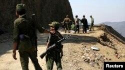 """果敢反政府武装""""缅甸民族民主同盟""""的一名15岁士兵和其他反政府武装士兵一道站岗。(2015年3月12日)"""