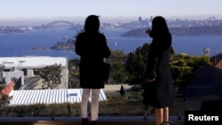 FILE - The Sydney Opera House and Harbour Bridge can be seen behind real estate agent LuLu Sun (R) as she escorts Bao Fang, a potential buyer from Shanghai, during an inspection of a property for sale in the Sydney suburb of Vaucluse, Australia, July 11,