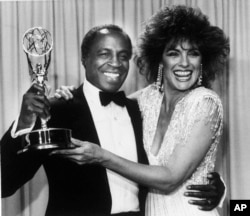 "FILE - Actor Robert Guillaume, star of ""Benson,"" gets a hug from Linda Gray of ""Dallas"" who presented him with the Emmy for outstanding lead actor in a comedy series, in Pasadena, Calif., Sept. 22, 1985."