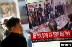 FILE - A man watches a TV broadcasting a news report on a high-level talks between the two Koreas at the truce village of Panmunjom, in Seoul, South Korea, Jan. 9, 2018.