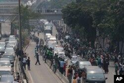 Ribuan pelayat berjajar di tepi jalan untuk menyaksikan iring-iringan kendaraan yang membawa jenazah Habibie ke Taman Makam Pahlawan Kalibata, Jakarta Selatan, hari Kamis (12/9).