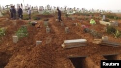 Residents look at fresh graves of people killed by what activists said were missiles fired by a Syrian Air Force fighter jet at a bakery in Halfaya, near Hama, Syria, December 24, 2012.