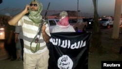 FILE - Islamic State militants display the group's flag in the city of Mosul, Iraq.