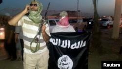 FILE - Militan ISIS memajang bendera kelompok tersebut di kota Mosul, Irak.