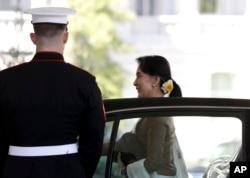 ຜູ້ນຳມຽນມາ ທ່ານນາງ Aung San Suu Kyi ຢ່າງອອກຈາກລົດ ໃນຂະນະທີ່ມາເຖິງທຳນນຽບຂາວ.